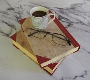 A cup of coffee and some books. A cup of coffee, glasses and some books on marble background royalty free stock photos