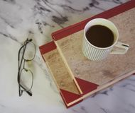 A cup of coffee and some books. A cup of coffee, glasses and some books on marble background royalty free stock images