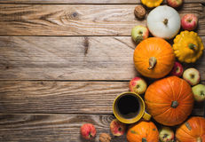 Cup of coffee and some pumpkins on wood background. Copy space royalty free stock image