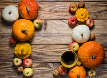 Cup of coffee and some pumpkins on wood background. Copy space stock photo