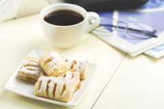 A cup of coffee and something sweet. To the morning newspaper - a nice start to the day royalty free stock images
