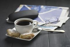 A cup of coffee and something sweet. To the morning newspaper - a nice start to the day royalty free stock photography