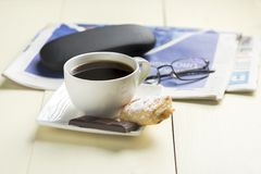 A cup of coffee and something sweet. To the morning newspaper - a nice start to the day royalty free stock image