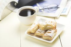 A cup of coffee and something sweet. To the morning newspaper - a nice start to the day royalty free stock photo