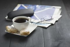 A cup of coffee and something sweet. To the morning newspaper - a nice start to the day stock photo