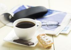 A cup of coffee and something sweet. To the morning newspaper - a nice start to the day stock photography