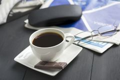 A cup of coffee and something sweet. To the morning newspaper - a nice start to the day stock images