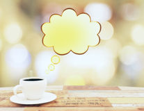 Cup of coffee with speach bubble on wooden table. Close up Stock Photos