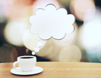 Cup of coffee with speach bubble on wooden table. Close up Royalty Free Stock Photography