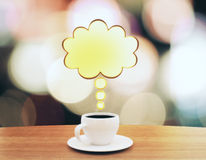 Cup of coffee with speach bubble on wooden table. Close up Stock Image