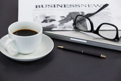 Cup of coffee, spectacles, closed laptop, newspaper and pen Stock Images