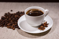 Cup of coffee with spices and beans on tablecloth Royalty Free Stock Photography
