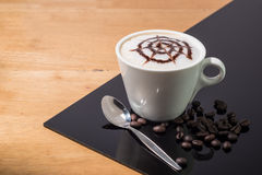 A cup of coffee with spider pattern  in a white cup  on wooden and blackboard background Stock Image