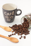 Cup of coffee and spilled coffee beans from glass jar Royalty Free Stock Images