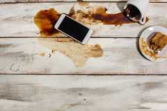 Cup of coffee spilled on wooden table Stock Photo
