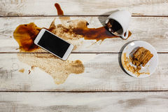 Cup of coffee spilled on wooden table Stock Photography