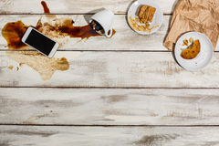 Cup of coffee spilled on wooden table Royalty Free Stock Images