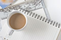 A cup of coffee on spiral notebook Stock Photos