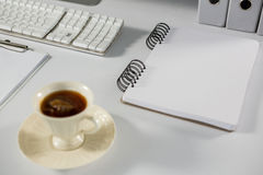 Cup of coffee with spiral notepad on table Stock Images