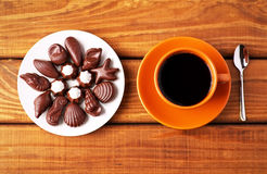 Cup of coffee with spoon and chocolate candies on table. Stock Images