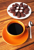 Cup of coffee with spoon and chocolate candies Royalty Free Stock Image