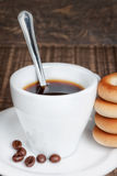 A cup of coffee with a spoon and dried bagels. Stock Image