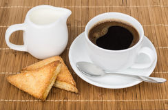 Cup of coffee, spoon, flaky cookies and jug milk Royalty Free Stock Photos