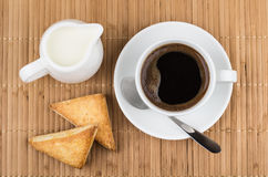 Cup of coffee, spoon, flaky cookies and milk Stock Photo