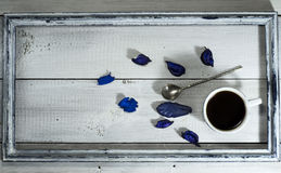 Cup of coffee and spoon in the old frame. On a white wooden background royalty free stock photo
