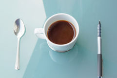Cup of coffee with spoon and pen on table Stock Image