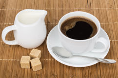 Cup of coffee with spoon, pieces sugar and milk jug Royalty Free Stock Images
