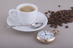 Cup of coffee with spoon, pocket watch and coffee beans Stock Image