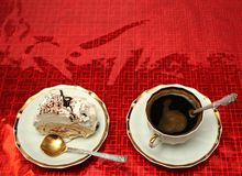 Cup of coffee with the spoon and a slice of a pie on a red backg Royalty Free Stock Photography