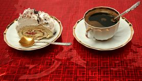 Cup of coffee with the spoon and a slice of a pie on a red backg Stock Image