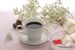 Cup of coffee and spring flowers on a pink background, good morning in a cozy home. Light and tender spring flowers and coffee with milk on a bright table will stock photo