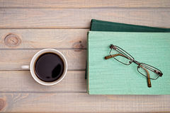 cup of coffee and a stack of books and glasses. Royalty Free Stock Photo