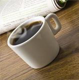 Cup of coffee and stack of newspapers Royalty Free Stock Images