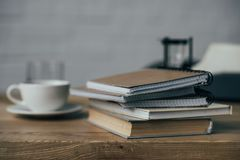 Cup of coffee and stack of notebooks. On work desk Stock Photo
