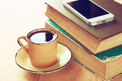 Cup of coffee, stack of old books and smartphone over wooden table, retro filtered image Stock Photos