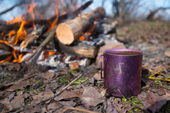 Cup with coffee is standing next to a campfire Royalty Free Stock Photo