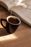 Cup of coffee, standing next to an open book Royalty Free Stock Image