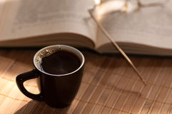 Cup of coffee, standing next to an open book Royalty Free Stock Photo