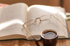 Cup of coffee, standing next to an open book, Stock Photos