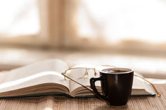 Cup of coffee, standing next to an open book Stock Photos