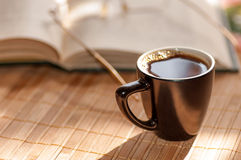 Cup of coffee, standing next to an open book Royalty Free Stock Photography
