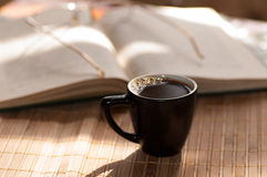 Cup of coffee, standing next to an open book Stock Image