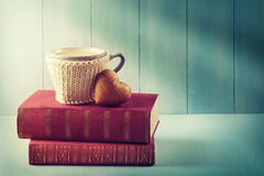 Cup of coffee standing on old books Stock Photos