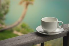 Cup of coffee standing on wooden balcony with lake background Stock Photo