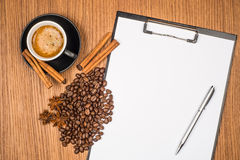 A cup of coffee, star anise, cinnamon and a clipboard Stock Images