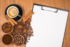 A cup of coffee, star anise, cinnamon and a clipboard Royalty Free Stock Photos
